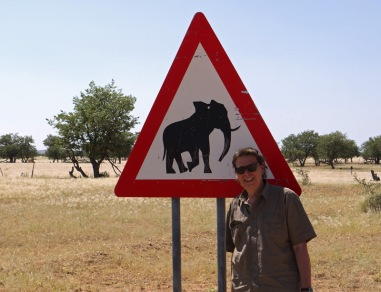 Andy Luck on assignment in Namibia beside elephant sign