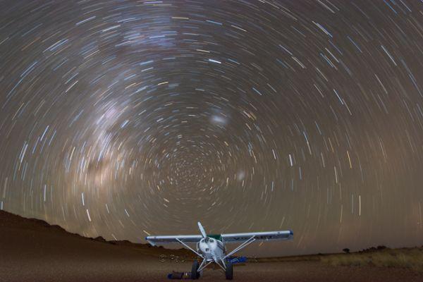 Stars wheel over Paul van Schalkwyk's aircraft. He often lands in remote desert locations in persuit of fine aerial photographs.