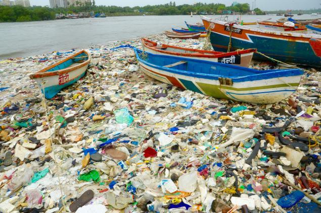 Lots of plastic rubbish beside boats in Mumbai.