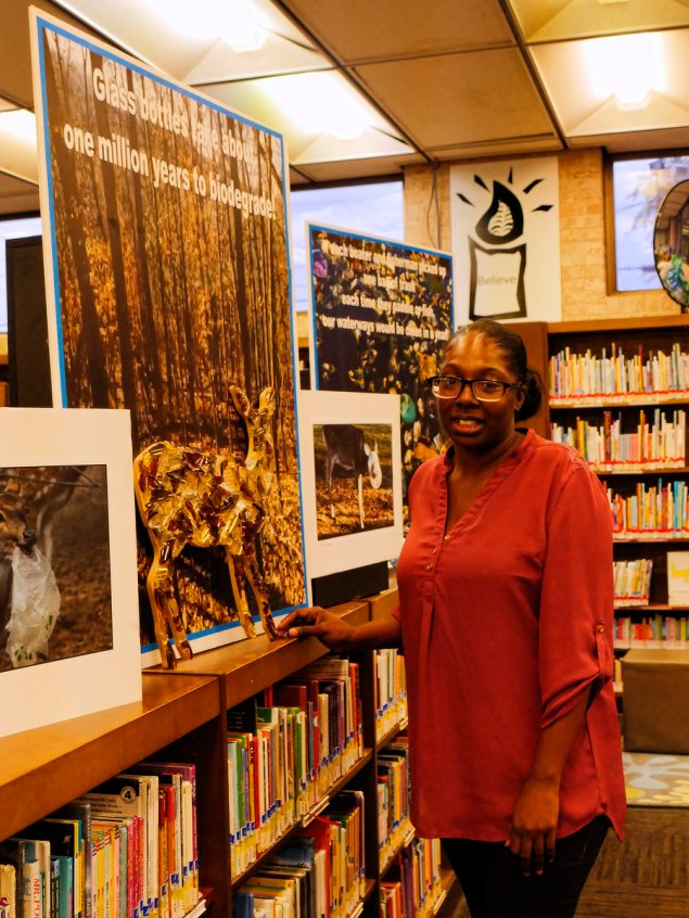 Librarian and artist Janare made this wonderful sculpture of a deer from discarded broken glass. Beside her is a NWF image of a deer with its head caught in a bag.