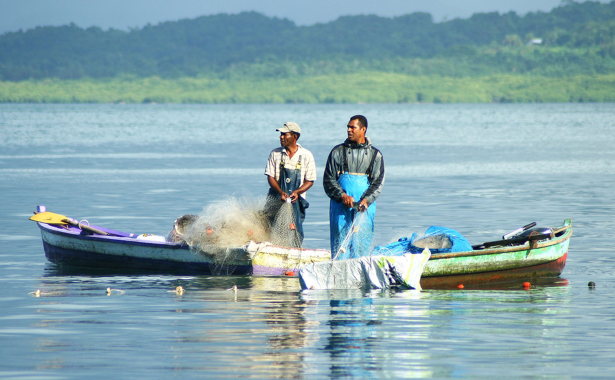 Local fishermen standing up in fishing boat; fishing will benefit from management of waste and chemical pollution.  Image and copyright Ian Lyons.